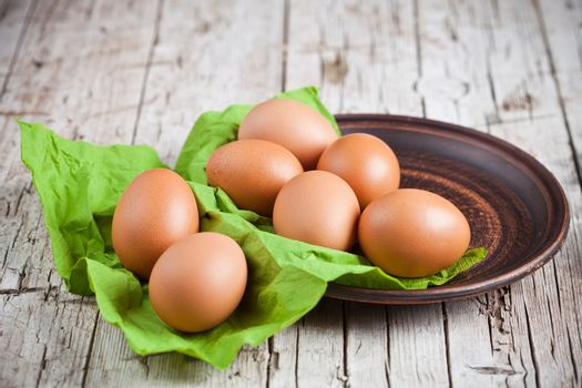 fresh brown eggs in plate and green napkin