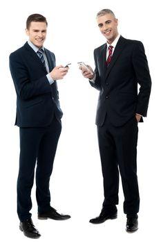 Smiling businessmen using cellphone