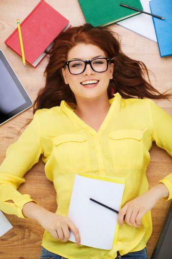 smiling female student with pencil and textbook