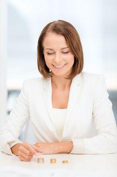 businesswoman putting euro coins into columns