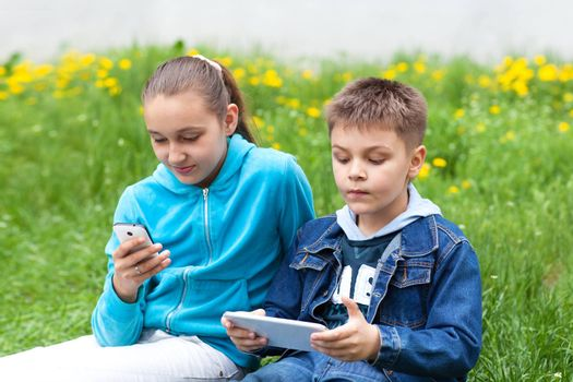 two children with gadgets outdoors