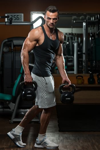 Muscular Man Exercise With Kettle Bell