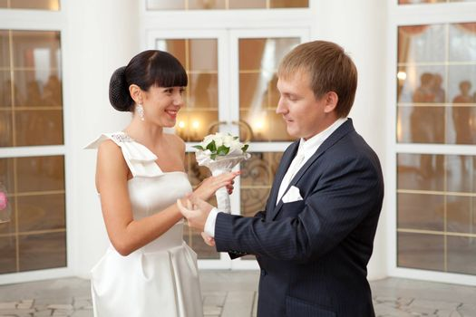 groom putting on a wedding ring to a bride