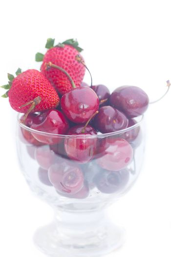 Cherries and strawberry in a glass bowl isolated on white