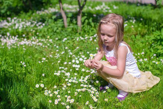 Little girl picking flowers in green glade