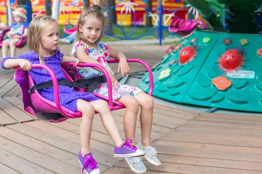 Two little cute sisters ride on carousel in the park
