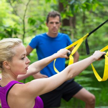 Young active people does suspension training with fitness straps outdoors in the nature.