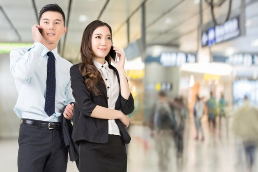 Asian business man and woman talking on cellphone