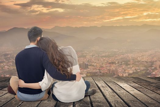 Asian young couple sit and hug together