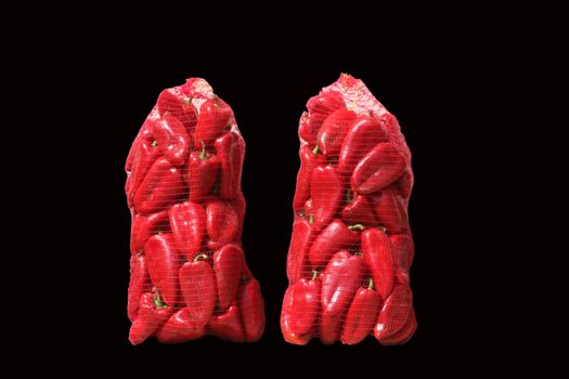 Red paprika in two sacks isolated on black