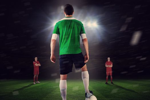 Football player in green with ball facing opposition