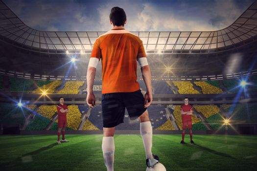 Football player in orange with ball facing opposition