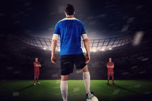 Handsome football player in blue jersey facing opposition