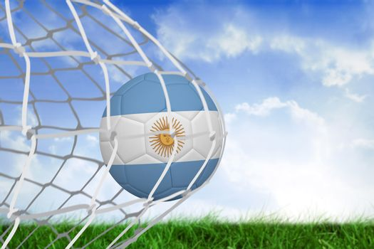 Football in argentina colours at back of net