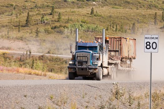 Heavy duty articulated industrial truck drives fast on remote gravel road throwing up dust