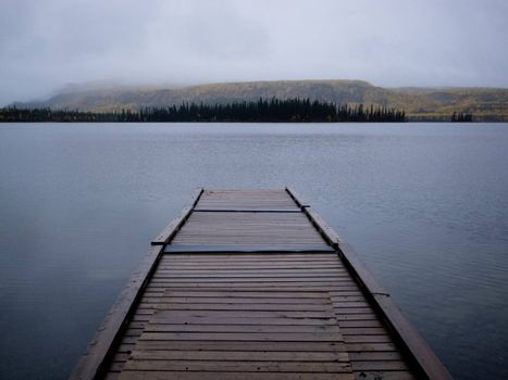 Twin Lakes, Yukon Territory, Canada, wooden floating boat dock on gray rainy day in autumn fall