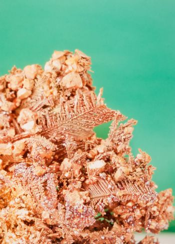 Native copper crystalline metal mineral rock against neutral green background