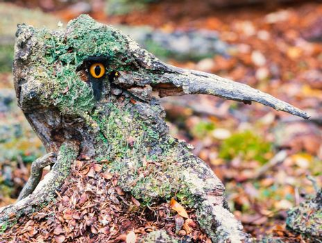 Scary forest fantasy long nose chimera with sparkling orange eye and lichens cover