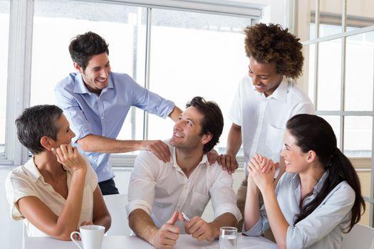 Attractive businessman praising coworker