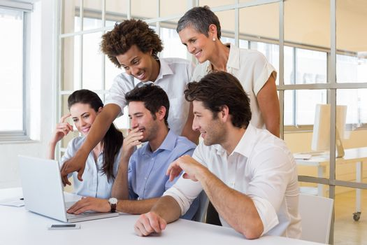 Workers laugh while looking at laptop