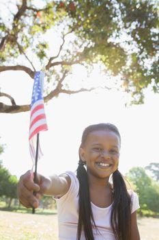 Little girl sitting on grass waving american flag