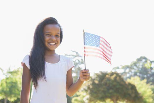 Little girl smiling at camera waving american flag