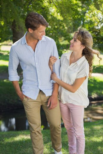 Cute couple walking arm in arm in the park smiling at each other