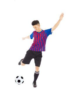 Young soccer player kicking ball