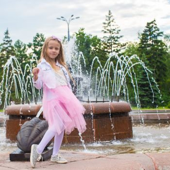 Little adorable girl in beautiful dress near fountain outdoor