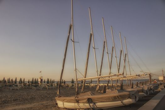 bathhouse and sailing boats on the seaside near the harbour channel of Cervia in Northern Italy on the Adriatic Sea