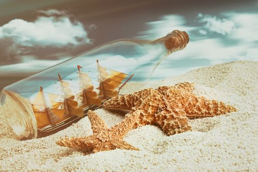 Bottle with ship inside on the beach