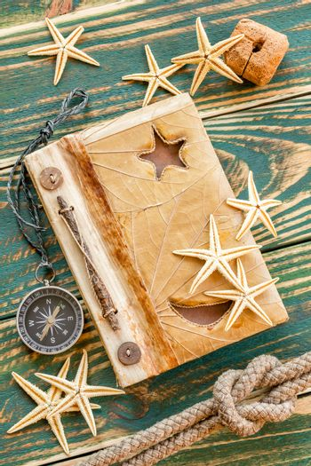 Old notepad with seashells on the deck