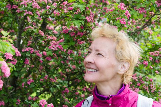 Portrait of a woman in a blossoming hawthorn