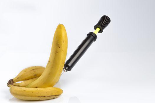 Male impotence metaphor: bicycle air pump pumping a  big banana among small bananas