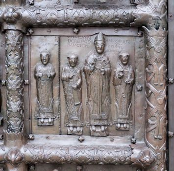 Ancient bronze gates of Magdeburg in Veliky Novgorod, Russia. Fragment of the bas-relief with bishop Alexander and deacons.