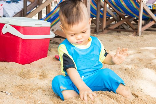 Asian boy playing sand on the beach, stock photo