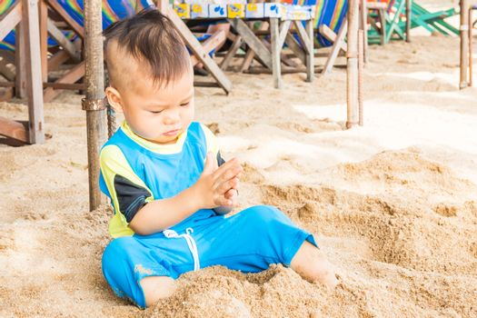Asian cute boy playing sand on the beach, stock photo
