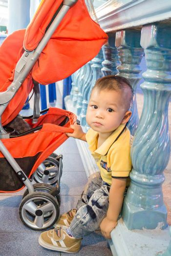Asian cute boy pose with baby stroller, stock photo