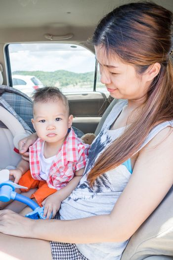 Asian boy sitting in the car with his mother, stock photo