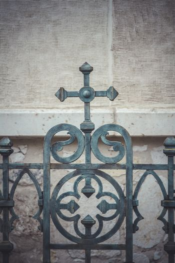 iron cross, fence with decorative metal flourishes