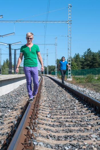Two trendy young men walking on the rail track
