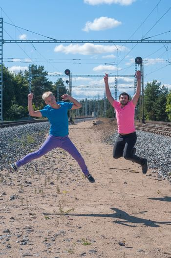 Two handsome young guys jumping near rail track