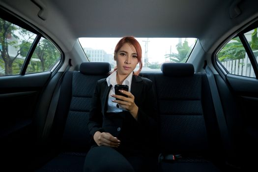 Beautiful young business asian woman using a smart phone in a car