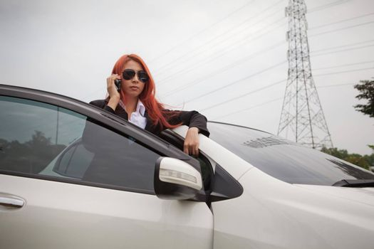 Beautiful young business asian woman using a smart phone and car