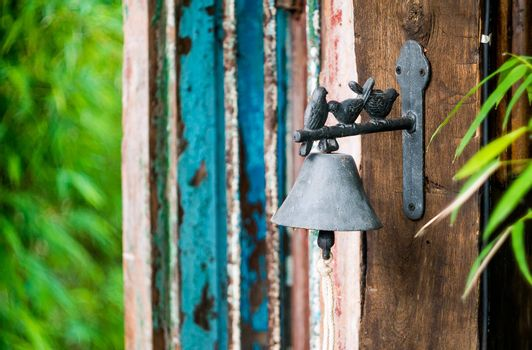 vintage ring bell decor with small bird at wooden door
