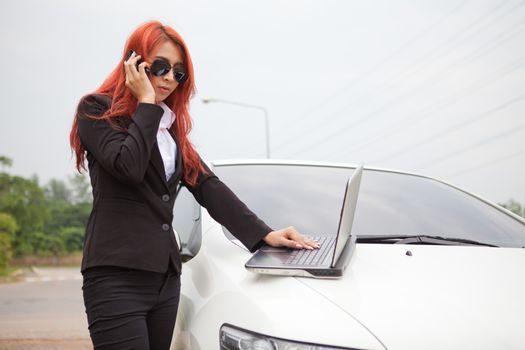 Beautiful young business asian woman using laptop and mobile phone and car