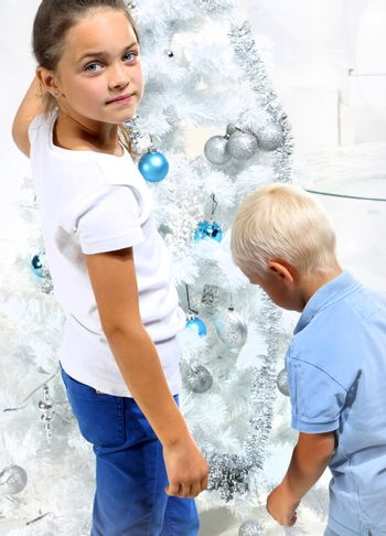 Brother and sister decorate the Christmas tree