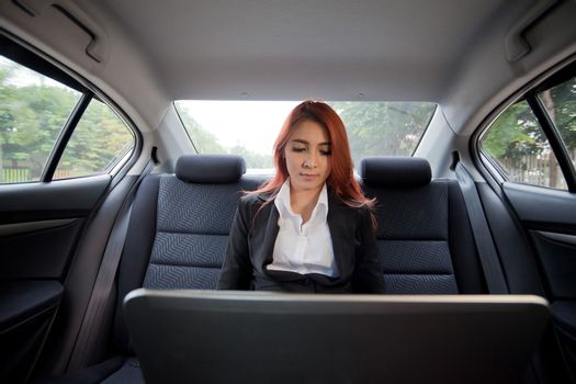 Beautiful young business asian woman using laptop in a car