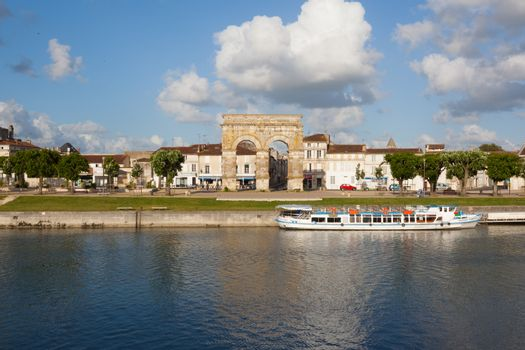 Panoramic view from the city of Saintes in the french region of Charente with the charente river, the city quay,a touristic boat and the roman germanicus arch