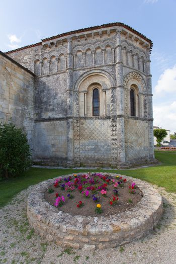 Abse and flowers of the romanesque Rioux church,Charente, France
